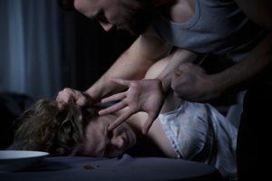 Eine Frau wird von einem Mann gewaltsam aufs Bett gepresst