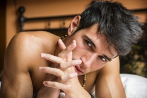 Junger sexy Mann liegt mit freiem Oberkörper auf dem Bett