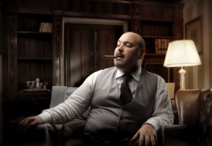 Dicker, älterer Mann sitzt auf einem Sessel und raucht Zigarre